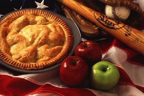 Ein Apfelkuchen neben 3 Äpfeln, einem Baseball und -schläger