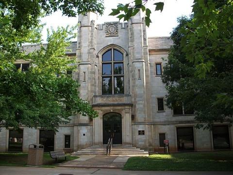 Blick auf ein altes Universitätsgebäude, links und rechts stehen Bäume; Public Domain, User: Brandonrush