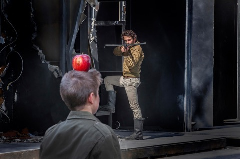 Im Vordergrund ein Junge mit einem roten Apfel auf dem Kopf, im Hintergrund ein Mann mit Armbrust; © Andy Stueckl, Passionstheater Oberammergau