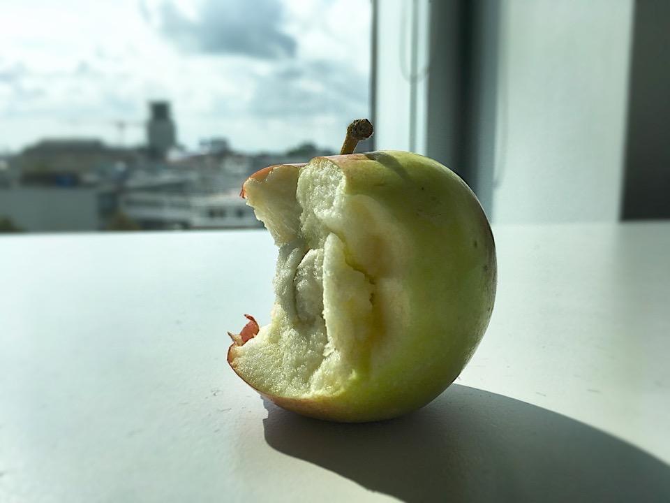 Ein angebissener Apfel liegt auf einem Tisch, im Hintergrund eine verschwommene Stadtsilhouette