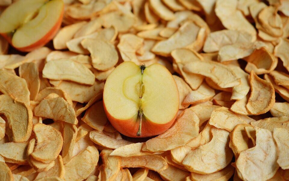 Ein halbierter Apfel liegt auf einer Fläche von getrockneten Apfelstücken; (C)Pixabay